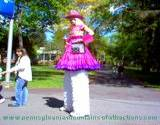 blonde woman on stilts and cowgirl outfit walking through Penn State Altoona Art Festival