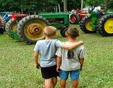 Two boys looking at a big green tractor at the Bedford Fair