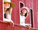 A couple of girls in old fashioned hats smiling out the window of a train at the Kutztown Festival
