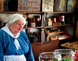 photo of a woman caring for the general store at Old Bedford Village Colonial Christmas event