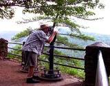 photo of man looking through a telescope to view the PA Grand Canyon