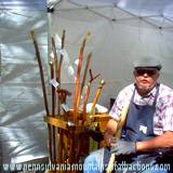 artist and canes he makes at booth at Penn State Art Festival