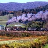 photo of steam locomotive traveling on tracks
