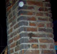 A clear ghostly orb caught on a chimney in the attic