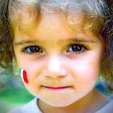 A little girl with Italian flax painted on her face at the Italian Food and Heritage Festival