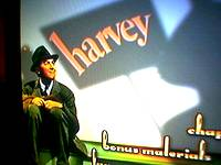 Jimmy Stewart sitting in front of a billboard of his famous movie Harvey