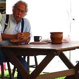 An elderly man painting his pottery at the Kutztown Fair