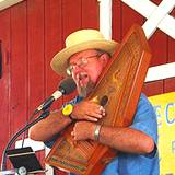 a man in a straw hat playing folk music on a autoharp at the Kutztown Festival