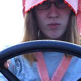 photo showing a girl wearing an old fashioned pink bonnet with a steering wheel in front of her at the Kutztown Festival