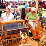 A photo of several rug makers working at their looms at the Kutztown Fesival