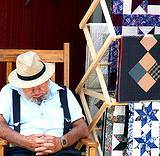 A photo of an elderly vender sleeping on a rocker at the Kutztown Fair