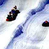 children snowtubing down a snowy slope