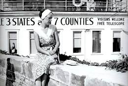 an old black and white photo of a young woman sitting in front of The U.S. Grand View Hotel