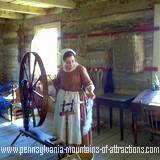 A woman operating a spinning wheel at The Old Bedford Village