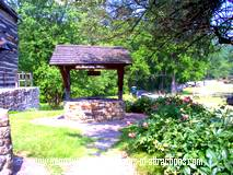 photo of an old well located next to a beautiful old church at Old Bedford Village